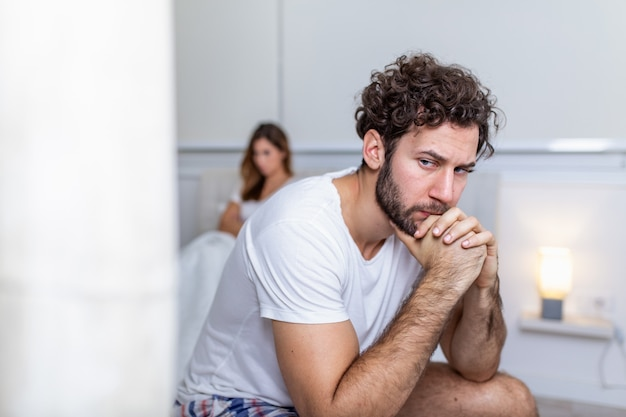 Sad thoughtful man after arguing with girlfriend. relationship difficulties, conflict and family concept, unhappy couple having problems at bedroom. sad guy sitting on bed Premium Photo