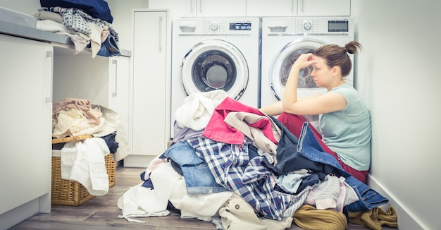 Sad tired woman in laundry room, blue tone Premium Photo