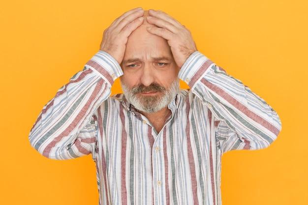 表情を強調し、禿げた頭に手をつないで、落ち込んで孤独を感じ、悲しみに襲われた灰色のひげを持つ悲しい不幸な老人。頭痛に苦しんで動揺した年配の男性 無料写真