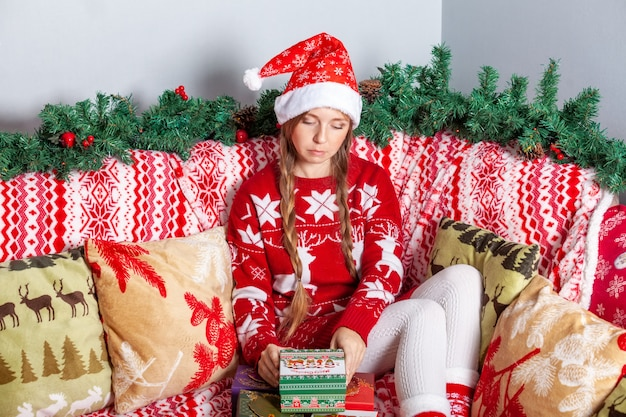 Sad unhappy girl in santa hat opens christmas gift boxes in new year decorations Premium Photo