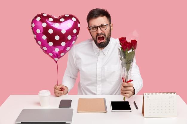 L'uomo triste e sconvolto riceve il rifiuto dal collega fino ad oggi, porta un mazzo di rose, san valentino, piange di disperazione, vestito con un'elegante camicia bianca Foto Gratuite