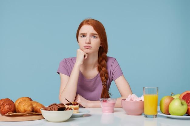 不満を持ってカメラを探している悲しい動揺赤毛の女の子、ダイエットについて考える 無料写真