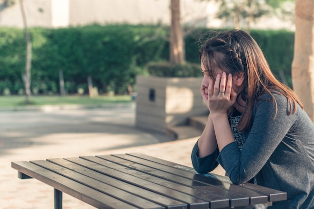 A sad, upset and worried woman sitting down alone outdoors Premium Photo