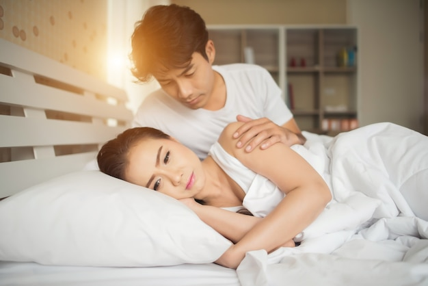 Sad woman and angry her boyfriend on the bed Free Photo