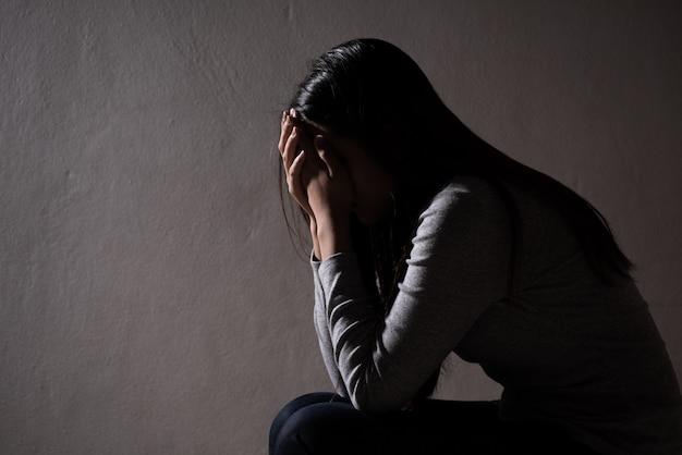 Грустная женщина закрыла лицо и заплакала. грустная женщина сидит в одиночестве в темной комнате. Premium Фотографии
