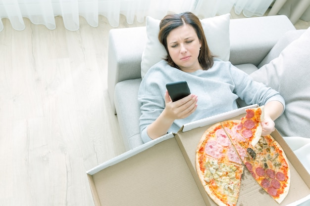 Sad woman eating pizza and holding phone laying on sofa at home, blue tone Premium Photo