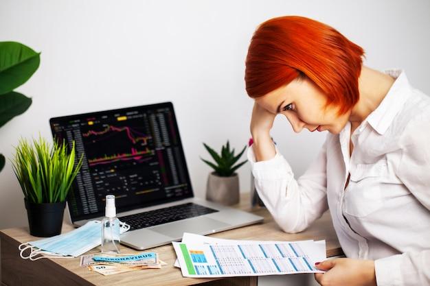 悲しい女性は流行のcovid-19の間に下落株価チャートを見ています Premium写真