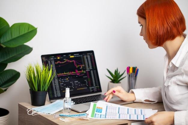 悲しい女性は、流行のcovid-19の間に下落株価チャートを見ています。 Premium写真