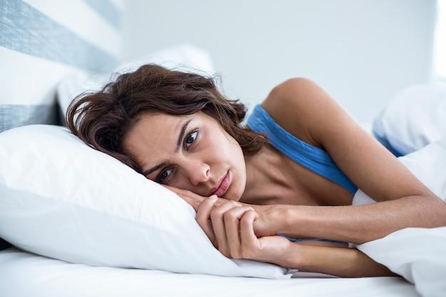 Sad woman lying on bed Premium Photo