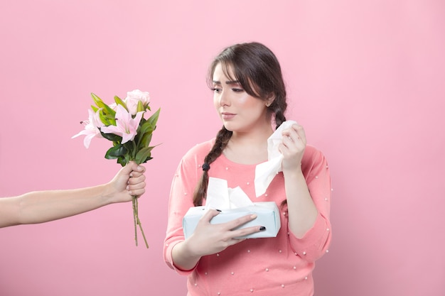 Sad woman receiving lily bouquet while holding napkins Free Photo
