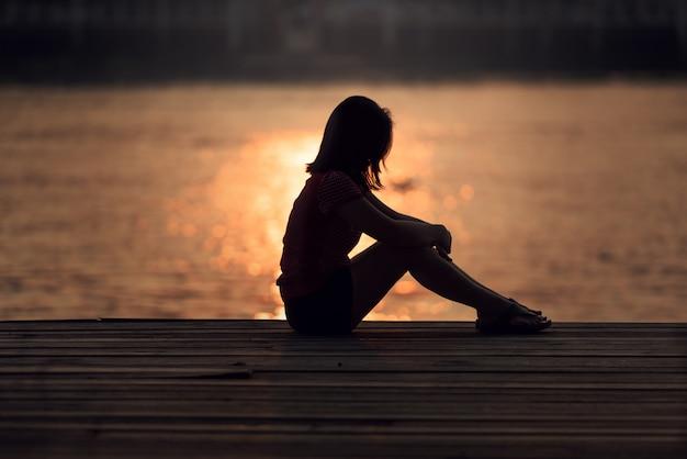 Sad woman silhouette worried at sunset Premium Photo