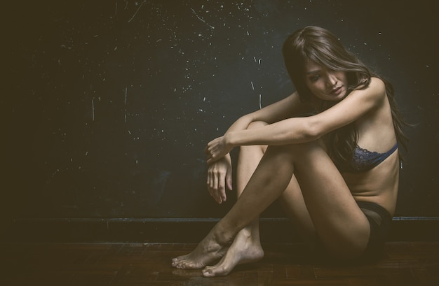 Sad woman sitting alone in a empty room Free Photo