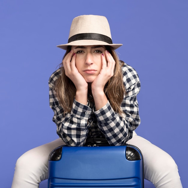 Sad woman sitting on baggage Free Photo