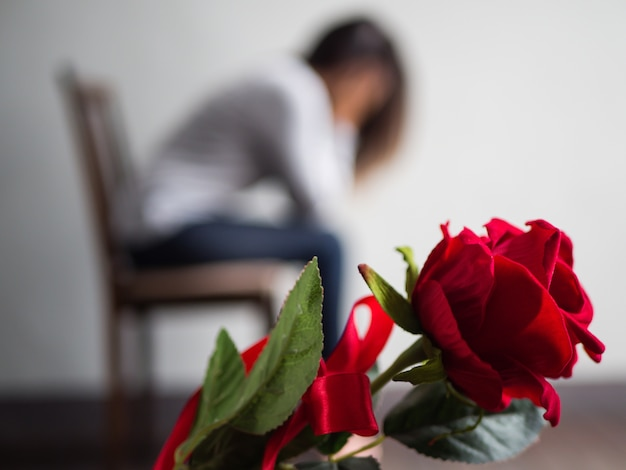 Sad woman sitting and crying with red rose in focus. Premium Photo