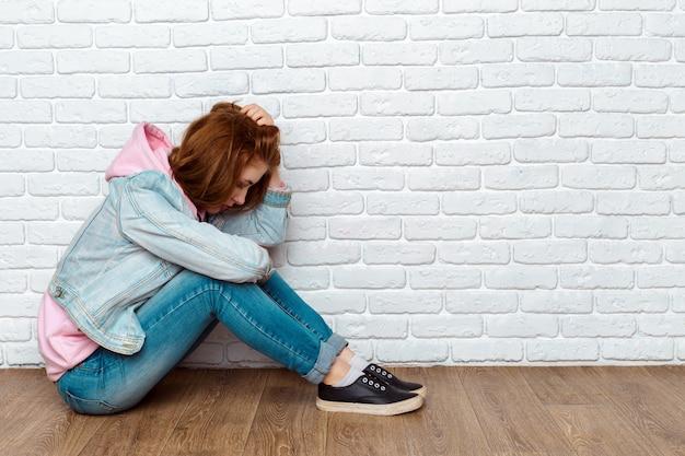 Sad woman sitting on floor near wall Premium Photo