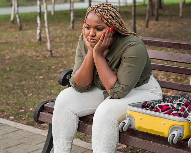 Triste donna seduta accanto al suo bagaglio aperto Foto Gratuite
