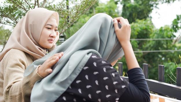 部屋に座っている悲しい女性。友達はあきらめません。悲しい少女と問題を解決するために友達をサポートしています。アジアの人々 Premium写真