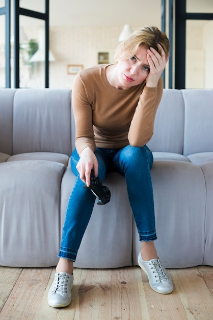 Sad woman sitting with joystick on couch Free Photo