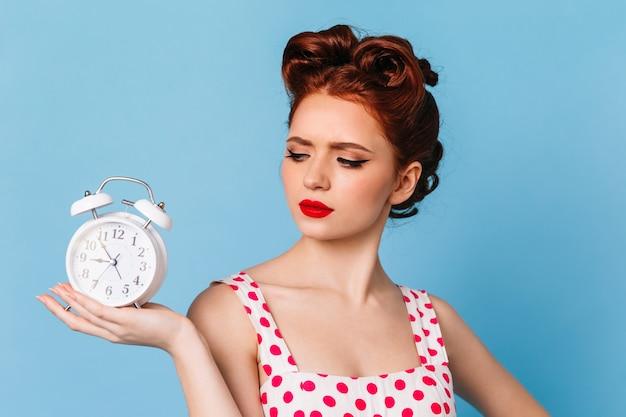 시계를보고 핀 업 헤어 스타일으로 슬픈 여자입니다. 푸른 공간에 포즈 폴카 도트 드레스에 매력적인 슬픈 소녀. 무료 사진