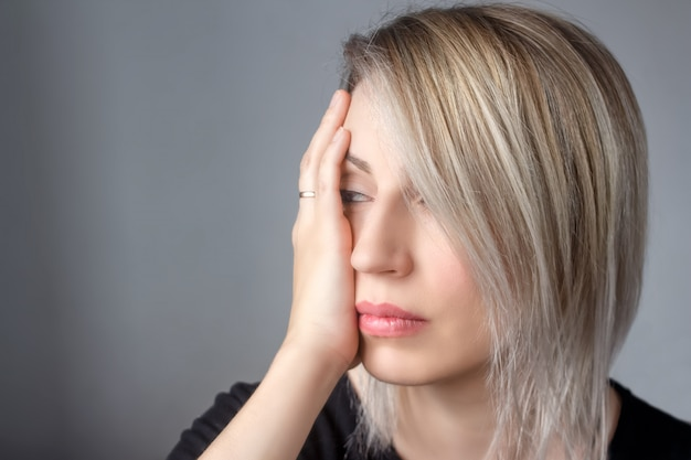 A sad woman with a ring on her hand presses her hand to the beating Premium Photo