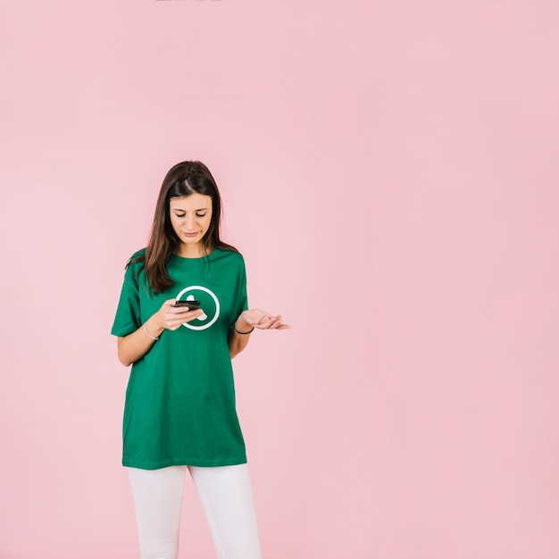Sad woman with smartphone shrugging against pink background Free Photo