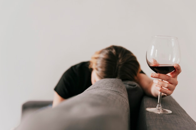 Sad woman with wine on couch Free Photo