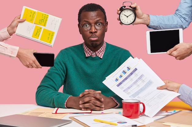 Sad young african american man dressed in green sweater, sits at desktop, hands with papers, alarm clock, touchpad, notepad with stickes Free Photo