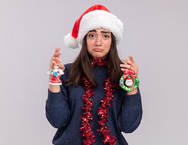 サンタの帽子と首に花輪を持つ悲しい若い白人の女の子はクリスマスツリーのおもちゃを保持します 無料写真