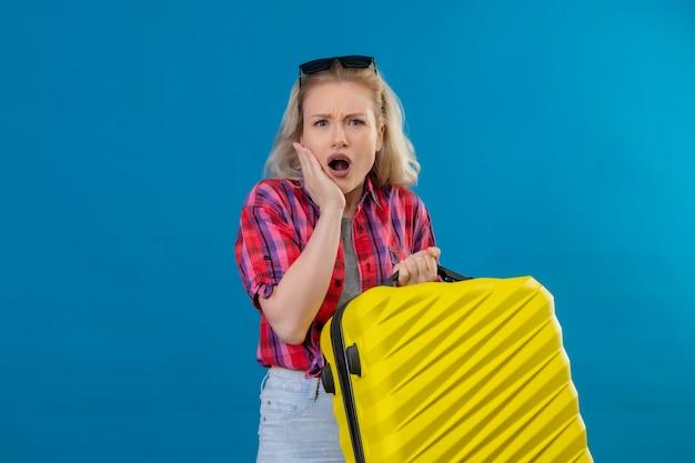 Triste giovane donna che indossa la camicia rossa e occhiali sulla testa che tiene la valigia ha messo la mano sulla guancia sulla parete blu isolata Foto Gratuite