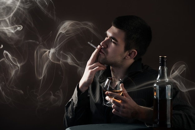 Sad young man beats an alcoholic drink from a chicken sitting in a dark room on a black background. Premium Photo