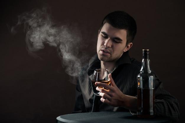 Грустный молодой человек выпивает алкогольный напиток из курицы, сидящей в темной комнате Premium Фотографии