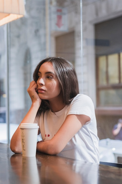 Sad young woman sitting in cafe with takeaway coffee cup on wooden table Free Photo