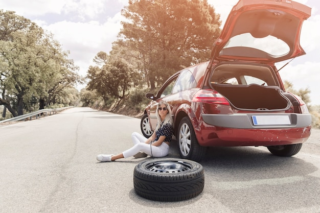 Sad young woman sitting near the broken down car on straight road Free Photo