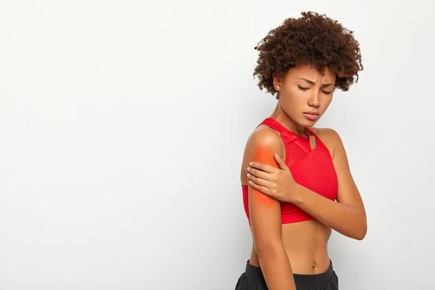 La giovane donna triste soffre di sensazione dolorosa nel muscolo del braccio, si trova lateralmente su sfondo bianco, spalla ferita durante la sessione di allenamento Foto Gratuite