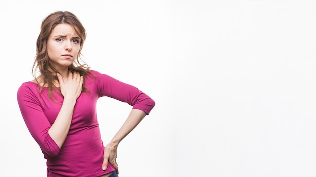Sad young woman with her hand on hips against white background Free Photo