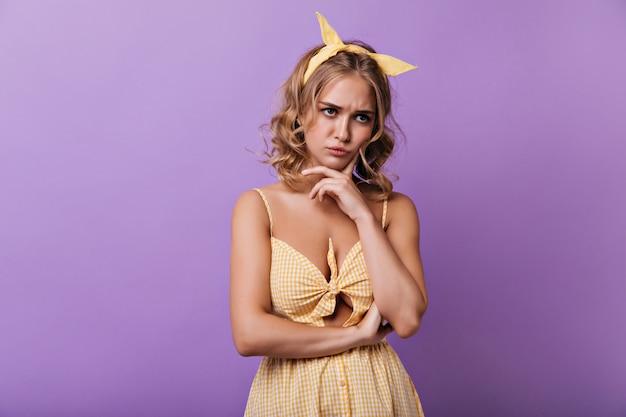 보라색에 포즈를 취하는 머리에 노란 리본으로 슬픈 젊은 여자. 여름 옷에 잠겨있는 곱슬 아가씨의 실내 초상화. 무료 사진