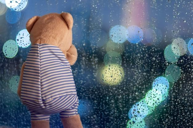 Sadly teddy bear crying at window in rainy day. Premium Photo