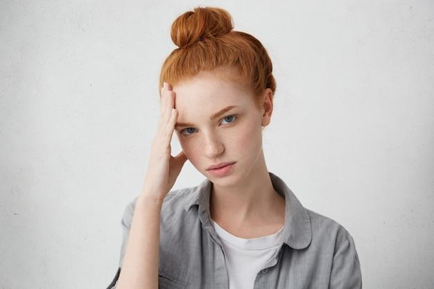 悲しみと悲哀。おでこを押しながら不機嫌そうな表情でお団子に生姜髪を着て悲しい少女 無料写真