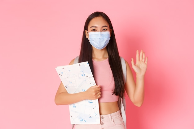 安全な観光、コロナウイルスのパンデミック中の旅行とウイルスの概念の防止。地図とbacpackが海外に行く、手を振ってこんにちは、医療マスクを着用するフレンドリーなかわいいアジアの女の子の観光客 Premium写真