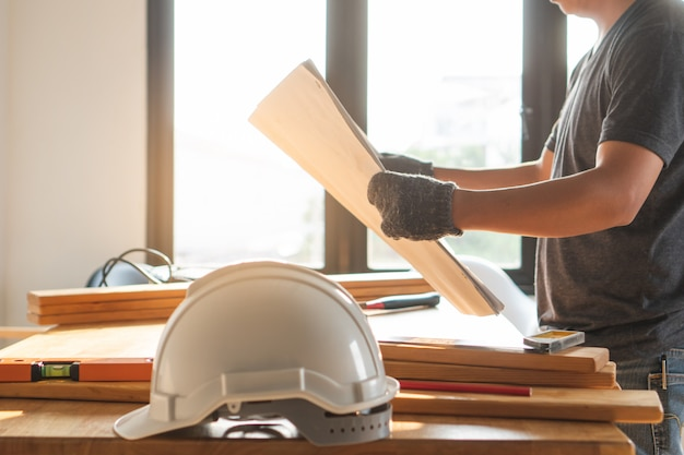Safety hard hat on the table and worker as background. Premium Photo