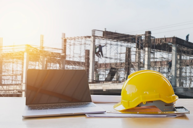 Safety helmet and computer laptop on table in concstruction site Premium Photo