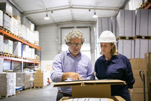 Ispettore di sicurezza che consulta il lavoratore logistico femminile durante la compilazione del modulo in magazzino. copia spazio, vista frontale. concetto di manodopera e ispezione Foto Gratuite