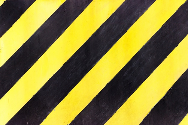 Safety stripes on construction site, black and yellow under construction sign over a grunge texture, top view Premium Photo