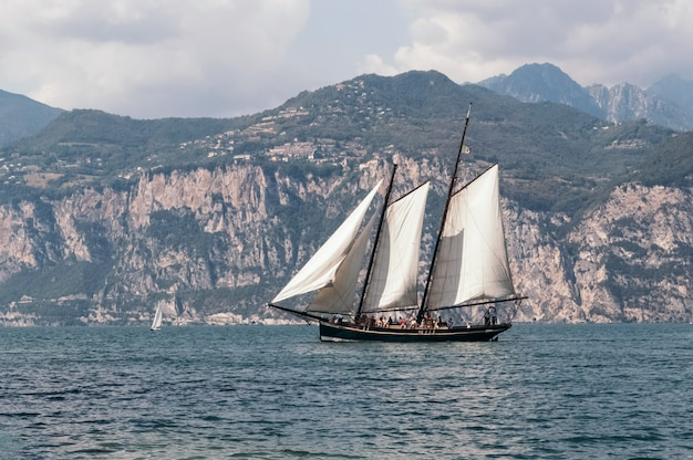 Sailboat floats on the background of a mountain range Premium Photo