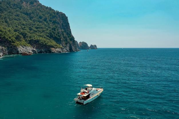 美しい大きな山の上の夕方の日光の下で海のヨット、贅沢な夏の冒険、地中海、トルコでのアクティブな休暇 無料写真