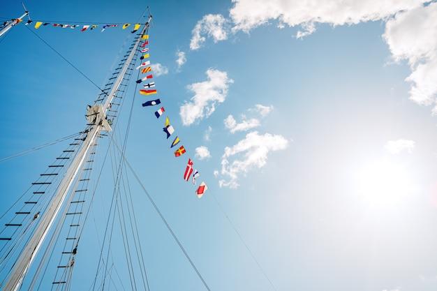Мачта парусника без вуали с флагами морских знаков, космосом для текста экземпляра. Premium Фотографии