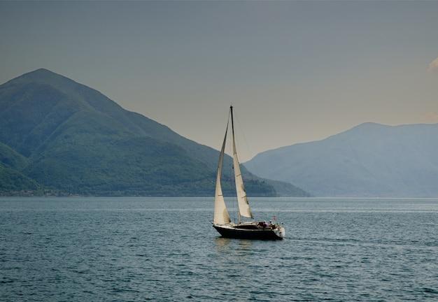 Barca a vela in mezzo al mare calmo sulle colline catturate in svizzera Foto Gratuite