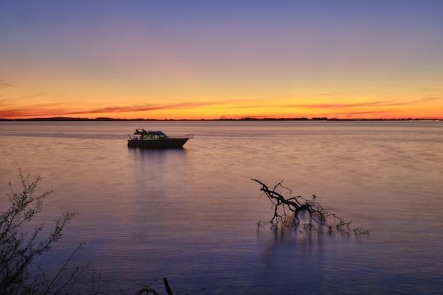 息をのむような夕日と穏やかな美しい海のセーリングボート 無料写真