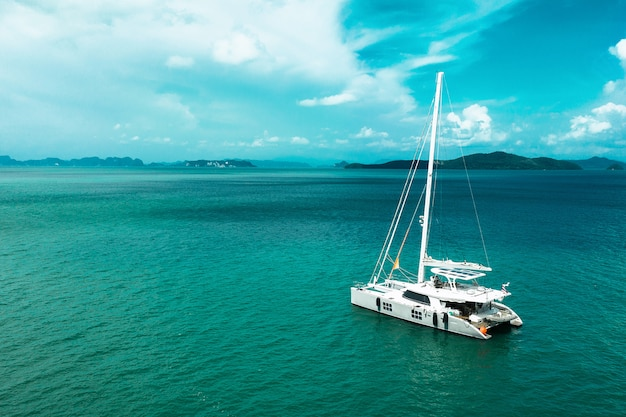 Sailing ship yachts with white sails at opened sea. aerial - drone view to sailboat in windy condition. Premium Photo