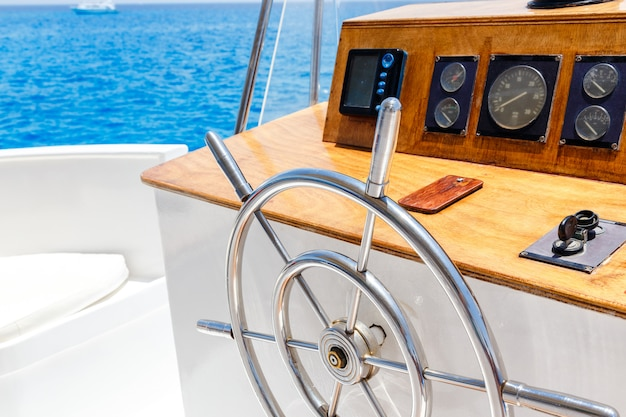 Sailing yacht control wheel and navigation implement. Premium Photo